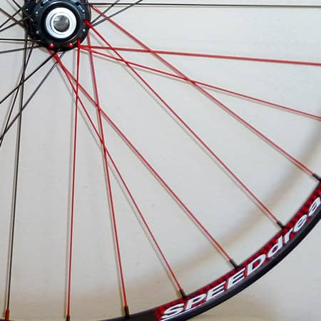 Red spokes on hand-built bike wheel